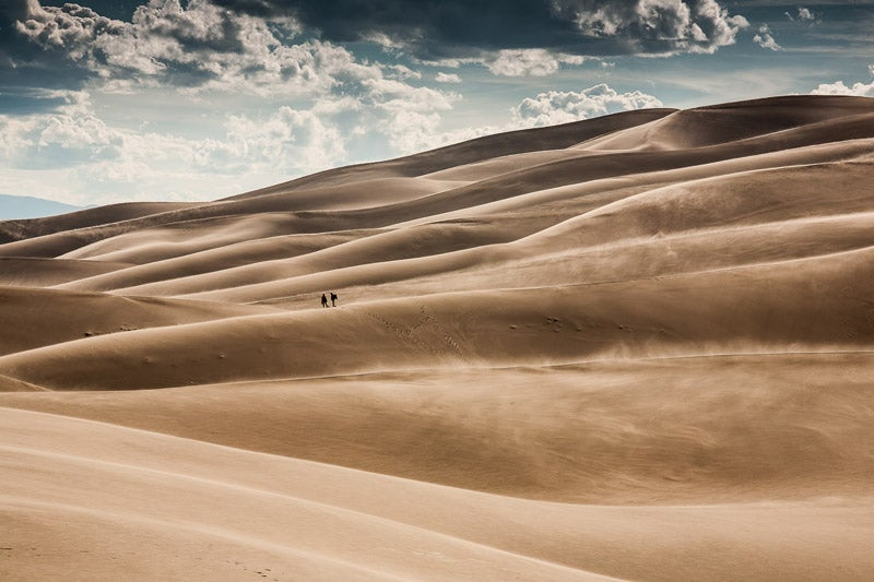 Hikers brave the windswept sand at Great Sand Dunes National Park